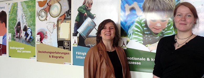 Die Leiterinnen des nifbe-Kooperationsprojektes vor der Plakatreihe, die im Projekt entstanden ist.