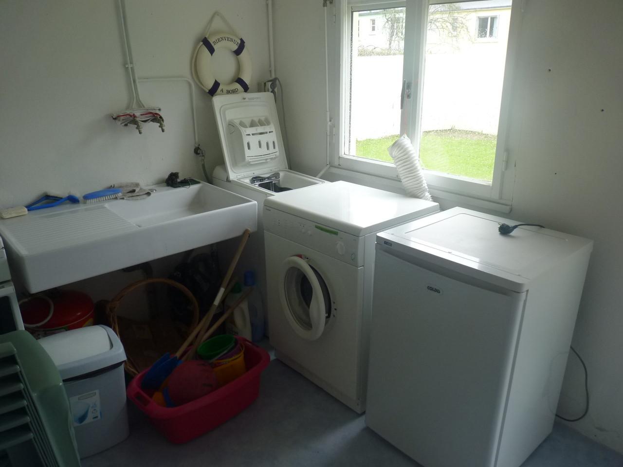 La buanderie avec lave-linge, séche-linge, congélateur 80l, gazinière avec four (absente photo)