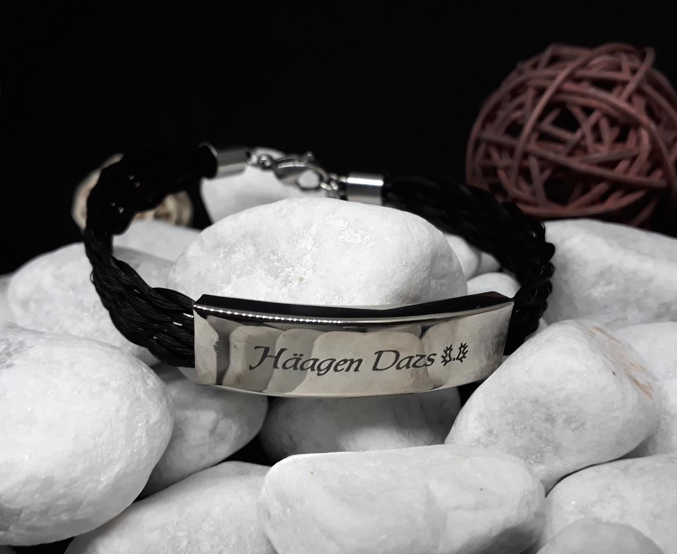F10-Gravur: Flach geflochtenes Armband aus 10 Strängen mit rechteckiger flacher Edelstahlhülse mit Gravur, mit Edelstahl-Karabinerverschluss - Preis: 59 Euro