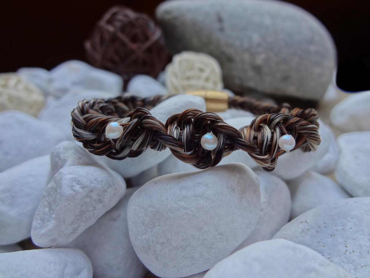Gedrehtes Armband mit crémefarbenen Kunstperlen und goldfarbenem Magnetverschluss