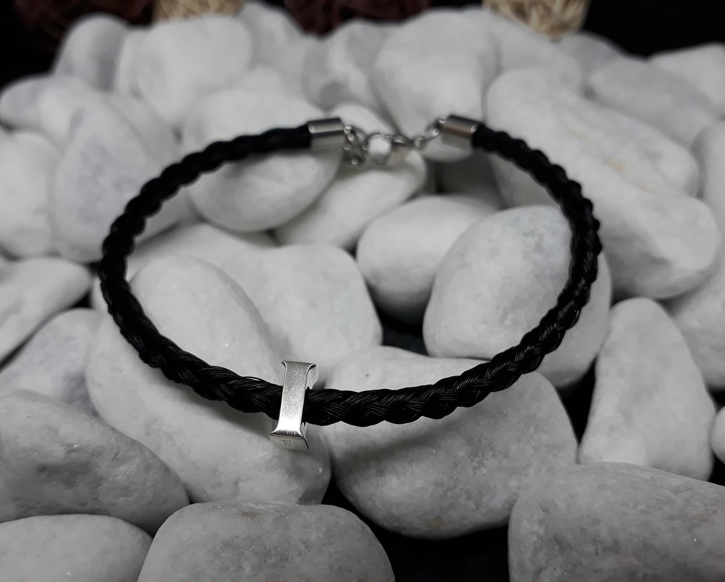 R6-Buchstabe: Rund geflochtenes Armband aus 6 schwarzen Strängen, mit Buchstaben-Perle aus 925er Silber, mit Edelstahl-Karabinerverschluss - Preis: 69 Euro
