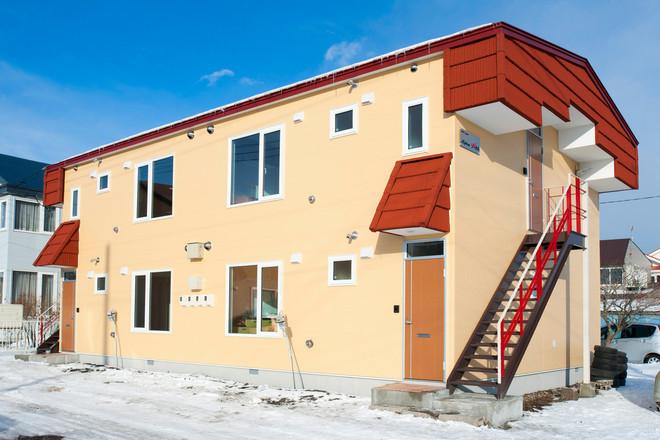 リノベーション後 クリーム色の外壁に屋根は赤に塗装されたアパート