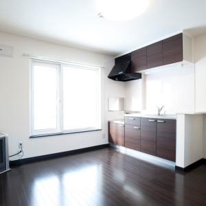 キッチンも濃い木目の建具に同じ色の床材 壁は真っ白