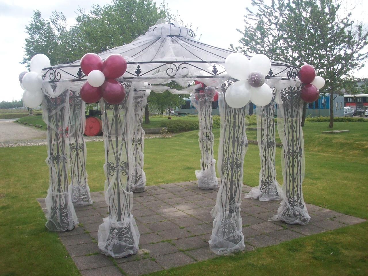 Dekorierter Pavllion. Die Befestigung der Ballon erforderte einiges an Erfahrung: Metallpavillion mit scharfen Kanten und rostigen Stellen und eine Stoffdekoration, die eine freie Erreichbarkeit der Fixierpunkte deutlich erschwerte.Dazu: Regenschauer/Wind