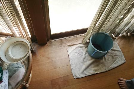 雨漏りの水を受け止めるバケツ