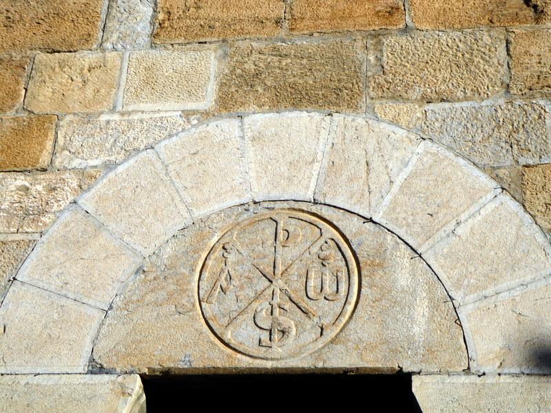 Chrisme (5 lettres grecques : khi, rhô, sigma, alpha et omega) ,de la petite porte d'entrée  percée en 1869