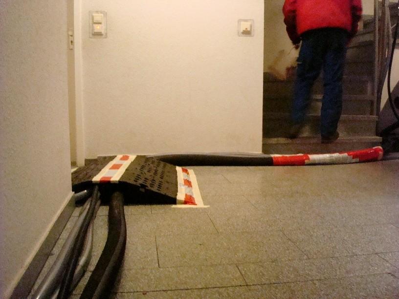 Absicherung der im Treppenhaus verlegten Schläuche für das Reinigungsmittel (Korund-Luft-Gemisch)