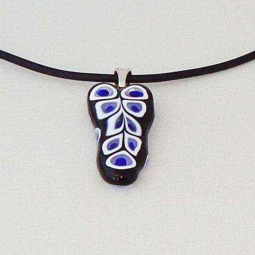 H3310.  Zwart met paars en wit millefiori glas. afm. ca. 3x1.5 cm.     €9.50.