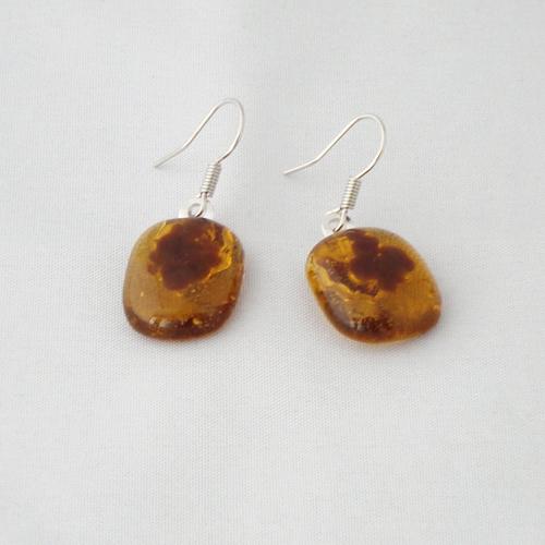 E1174. Helder amber glas met bruine korreltjes. afm. ca. 1.5x1.5 cm.   €6.50.