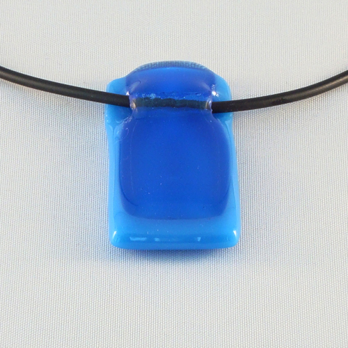 H3185. Blauw helder en opaal glas. afm. ca. 4.5x2 cm. inclusief rubber koord, want een ketting kan niet door de tunnel.    €9.50.