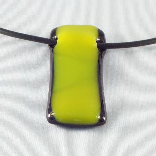 H3175. Zwart opaal glas met geel/groen opaal glas. afm. ca. 4.5x2 cm. inclusief rubber koord, want een ketting kan niet door de tunnel.     €9.50.