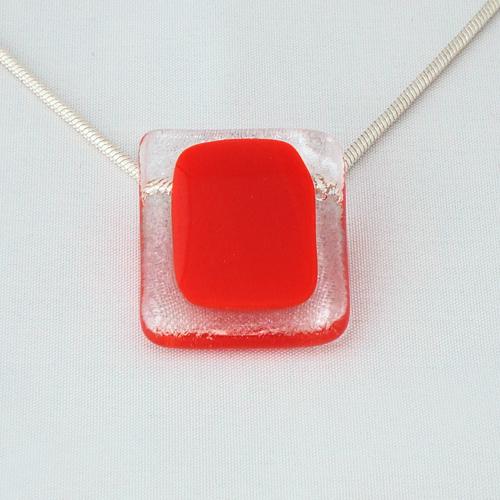 H3216. Helder glas met rood opaal glas. afm. ca. 3x2.5 cm. alleen te dragen met ketting met diameter tot 2 mm.     €9.50.