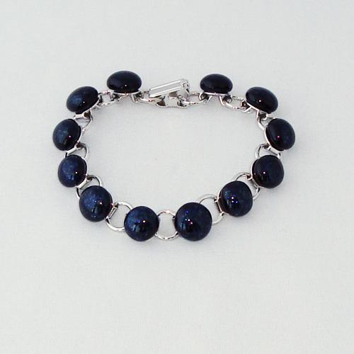 P1162. Schakelarmband met donker blauwe glitter steentjes.     €19.50.
