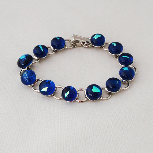 P1207. Schakelarmband met blauw glas en blauw/groen dichroic steentjes.     €19.50.