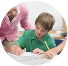 Boy writing in notebook while teacher observes