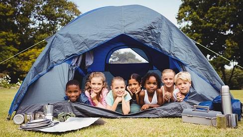7 Kinder liegen in einem Zelt und freuen sich: Campingplatz-Urlaub boomt in der Corona-Zeit. Gut geschützt mit einer Camping-Reiseversicherung der ERGO.