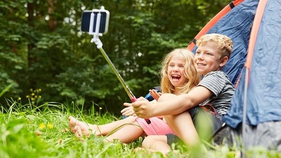 Campingplatz mit Zelt und zwei Kindern, die Selfies machen