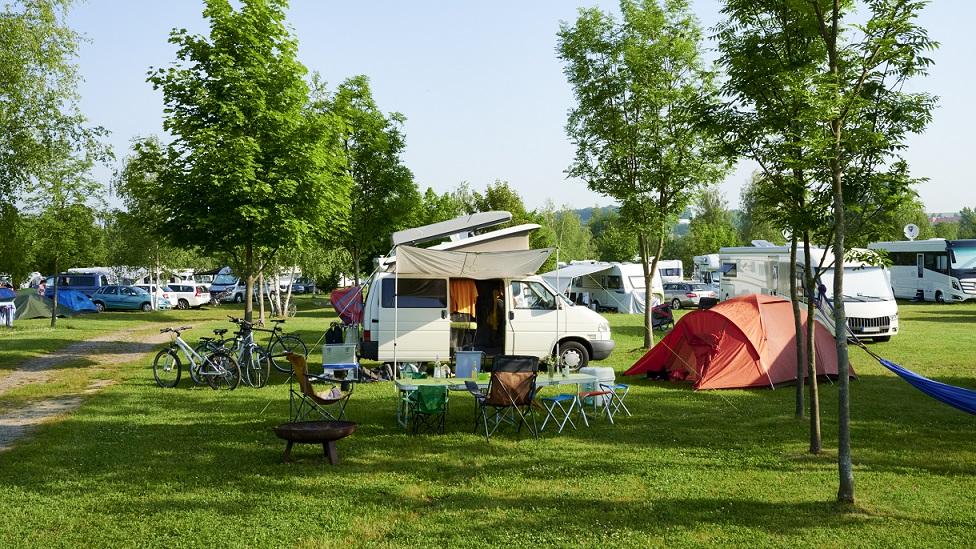 Campingplatz mit Zelten, Autos, Wohnmobilen und Wohnwagen