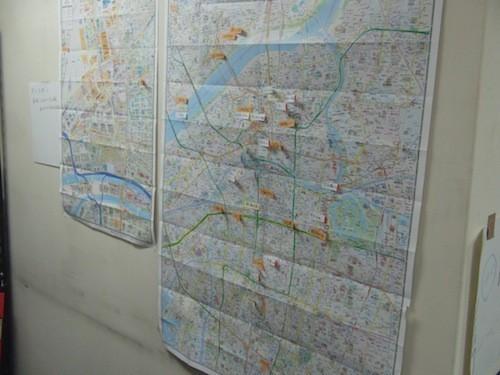 事務所の壁に貼られた大阪市内の地図。設置できそうな場所に貼られた付箋は、進行状況別に色分けされています。