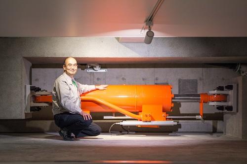 写真2 揺れの大きさに応じて自動的に性能を変える新開発の免震装置(油圧ダンパー)前で