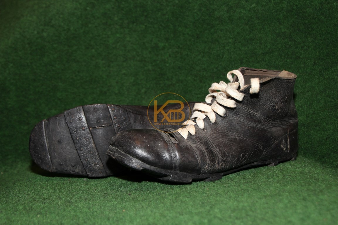 Hohe schwarze Fußballschuhe mit genagelten Lederriemen als Stollen.