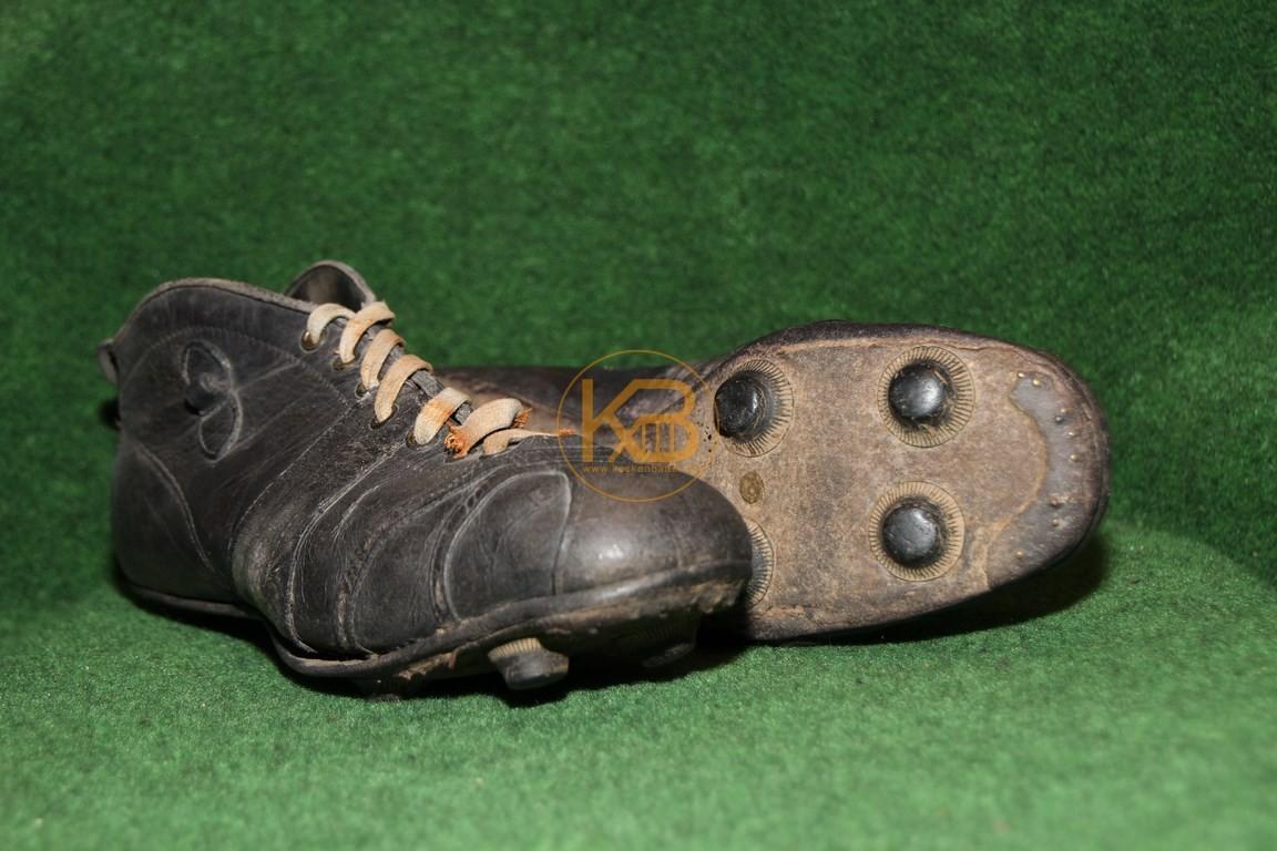 Hoher schwarzer Fußballschuh mit einer ersten Form der wechselbaren Schraubstollen.