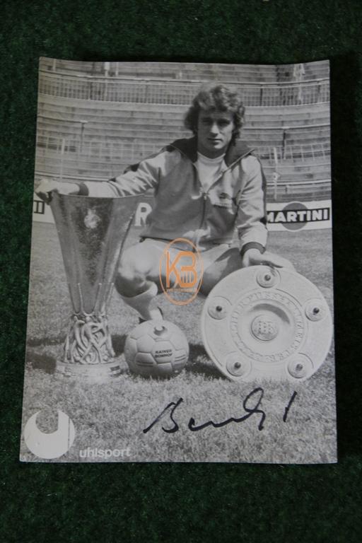 Original Autogrammkarte von Rainer Bonhof im Trikot von Borussia Mönchengladbach mit der Meisterschale und dem UEFA Pokal aus dem Jahr 1975