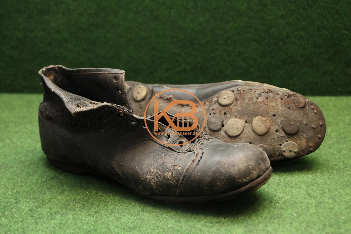Alte Fußballschuhe mit Stahlkappe und genagelten Stollen aus den 1930er Jahren im stark bespielten Zustand.
