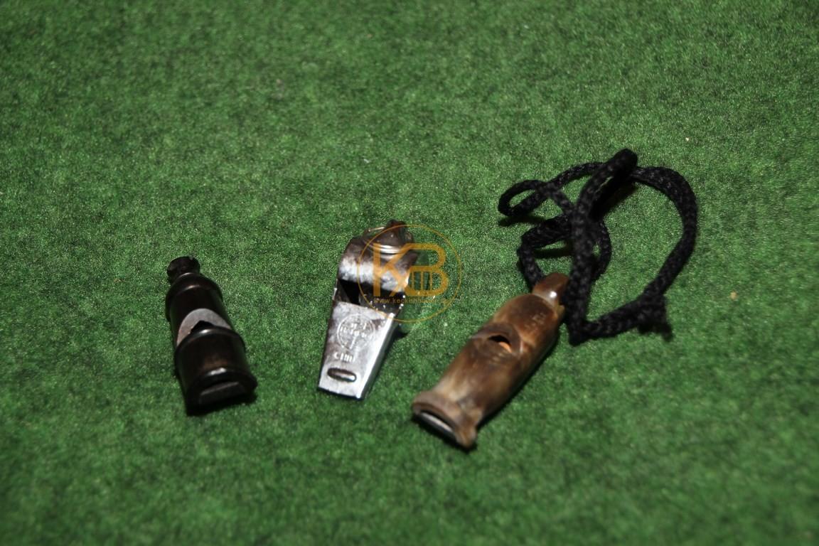 Drei alte Schiedsrichterpfeifen aus Hartplastik, Metall und Horn.