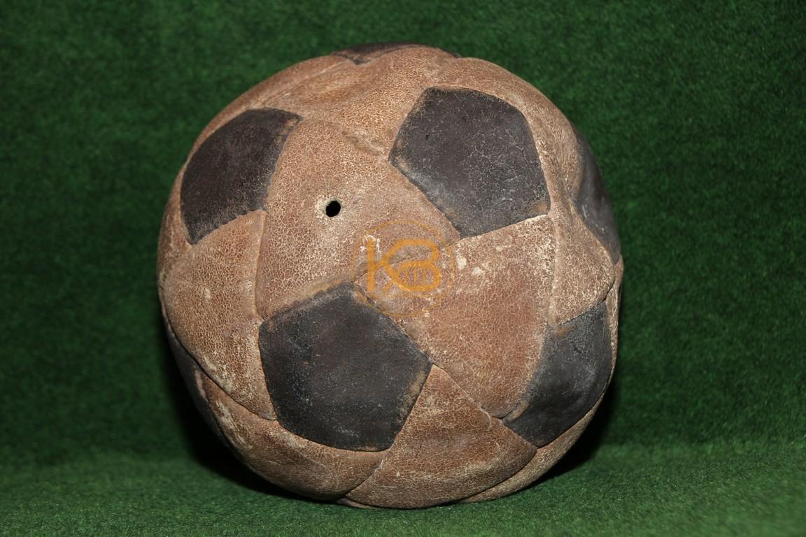 Alter schwarz weißer Fußball der hier im Besonderen aus schwarzen Waben und weißen Dreiecken gefertigt wurde.