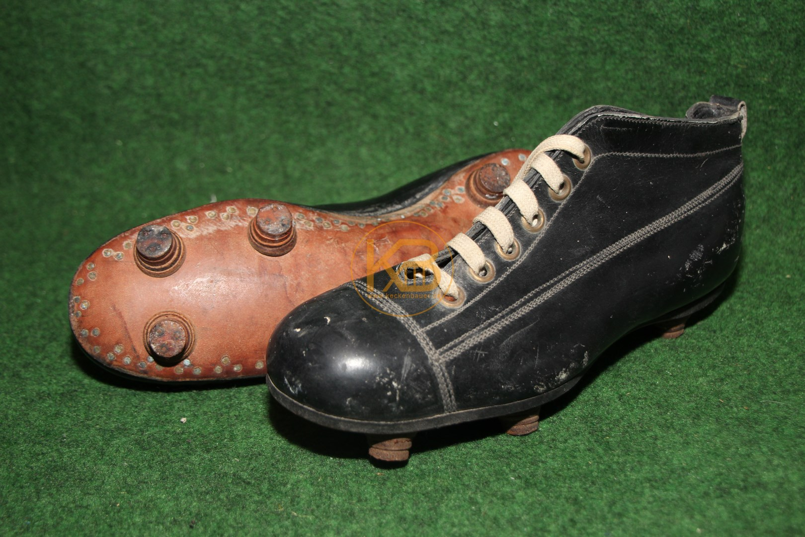 Schwarze hohe Fußballschuhe mit genagelten Stollen aus den 1920er Jahren.