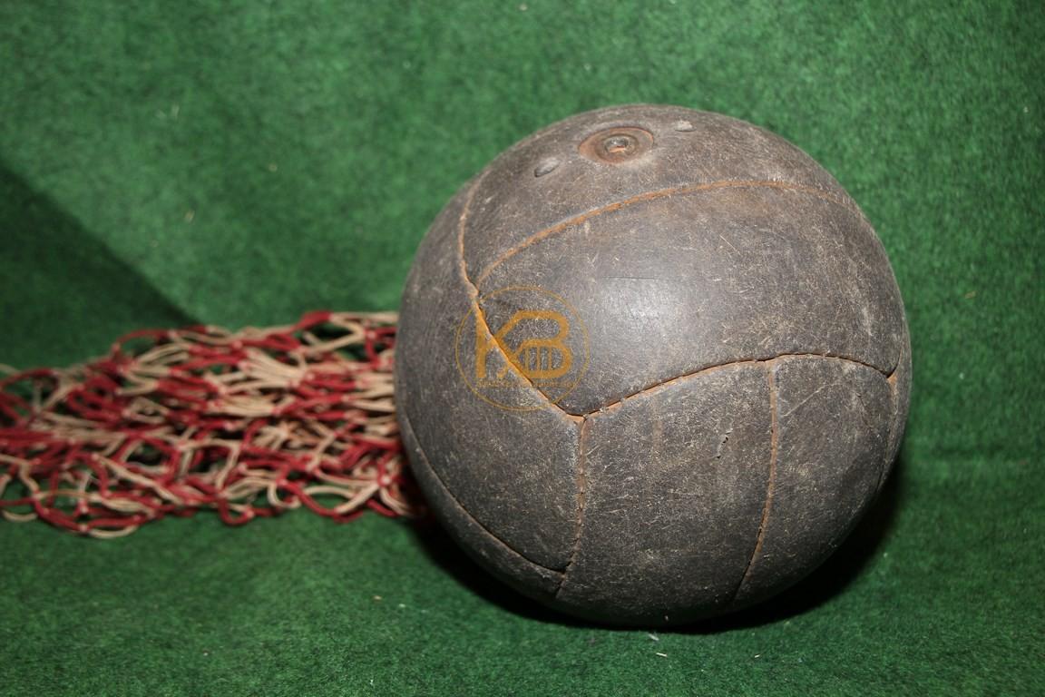 Alter Lederfußball der aus den bekannten Längsstreifen genäht ist mit dem original Ballnetz.