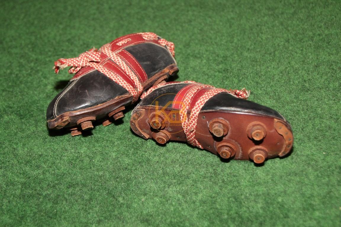 Alte mini Fußballschuhe mit genagelten Stollen.