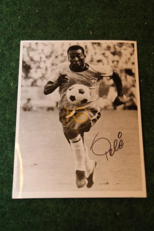 Original Autogramm von Pelé auf einem Pressefoto.