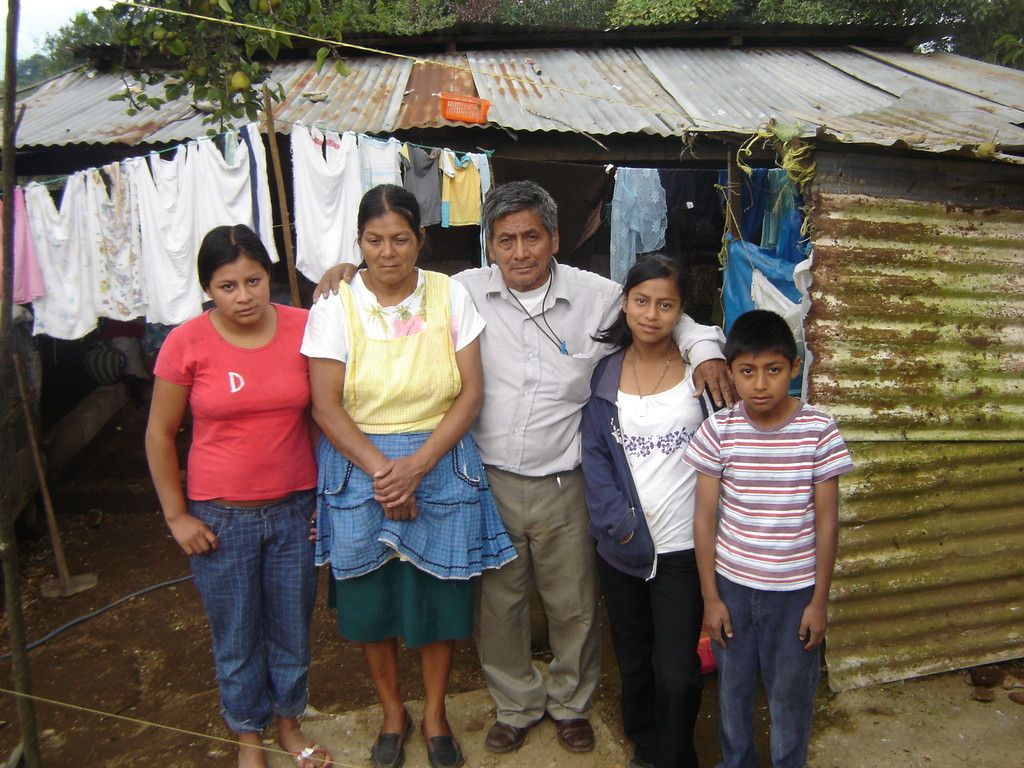 Mundo family in front of their old home