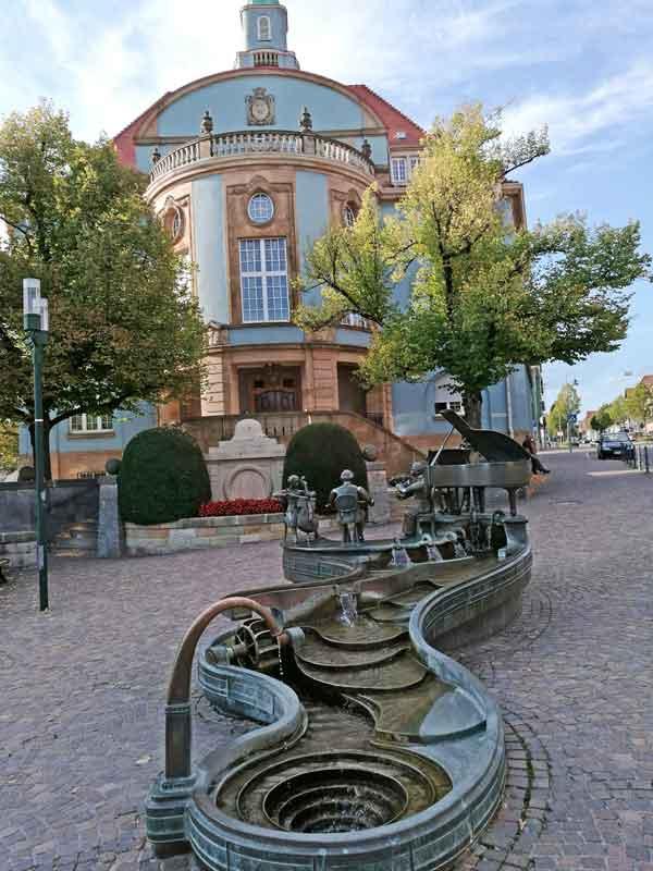 """Nach dem Stadtbrand wurde das Rathaus I 1910/11 im Jugendstil wieder aufgebaut. 1989, anlässlich der 1100-Jahr-Feier, wurde die Neugestaltung des Rathausplatzes mit dem """"Musikantenbrunnen"""" des Künstlers Bonifatius Stirnberg vollendet."""