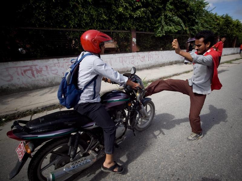 Ein Demonstrant in Nepal versetzt einem Motorrad während eines Streiks einen Tritt. Foto: Narendra Shrestha