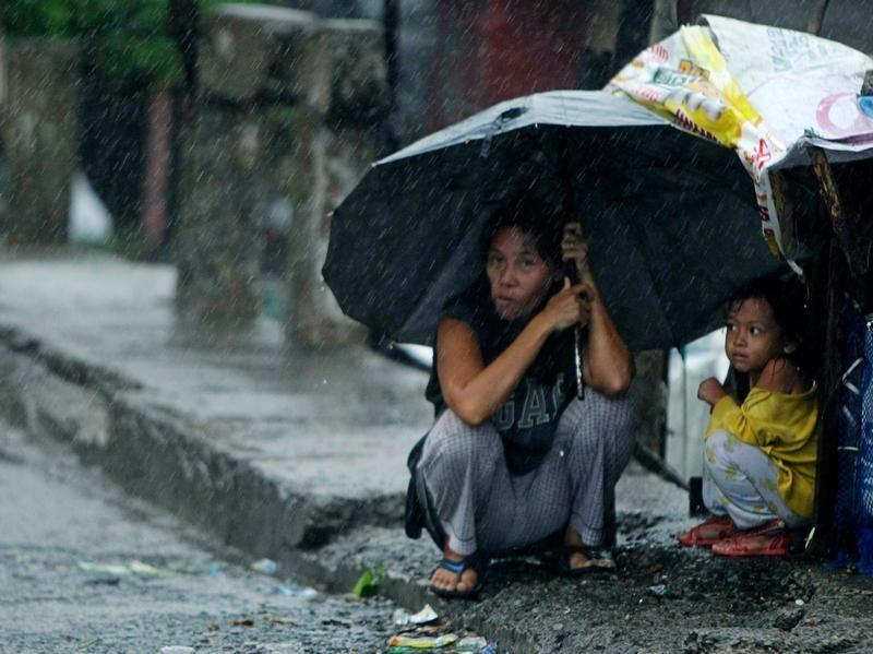 Es hört nicht auf: Eine Mutter und ihr Kind warten südlich der philippinischen Hauptstadt Manila auf eine Regenpause. Foto: Francis R. Malasig