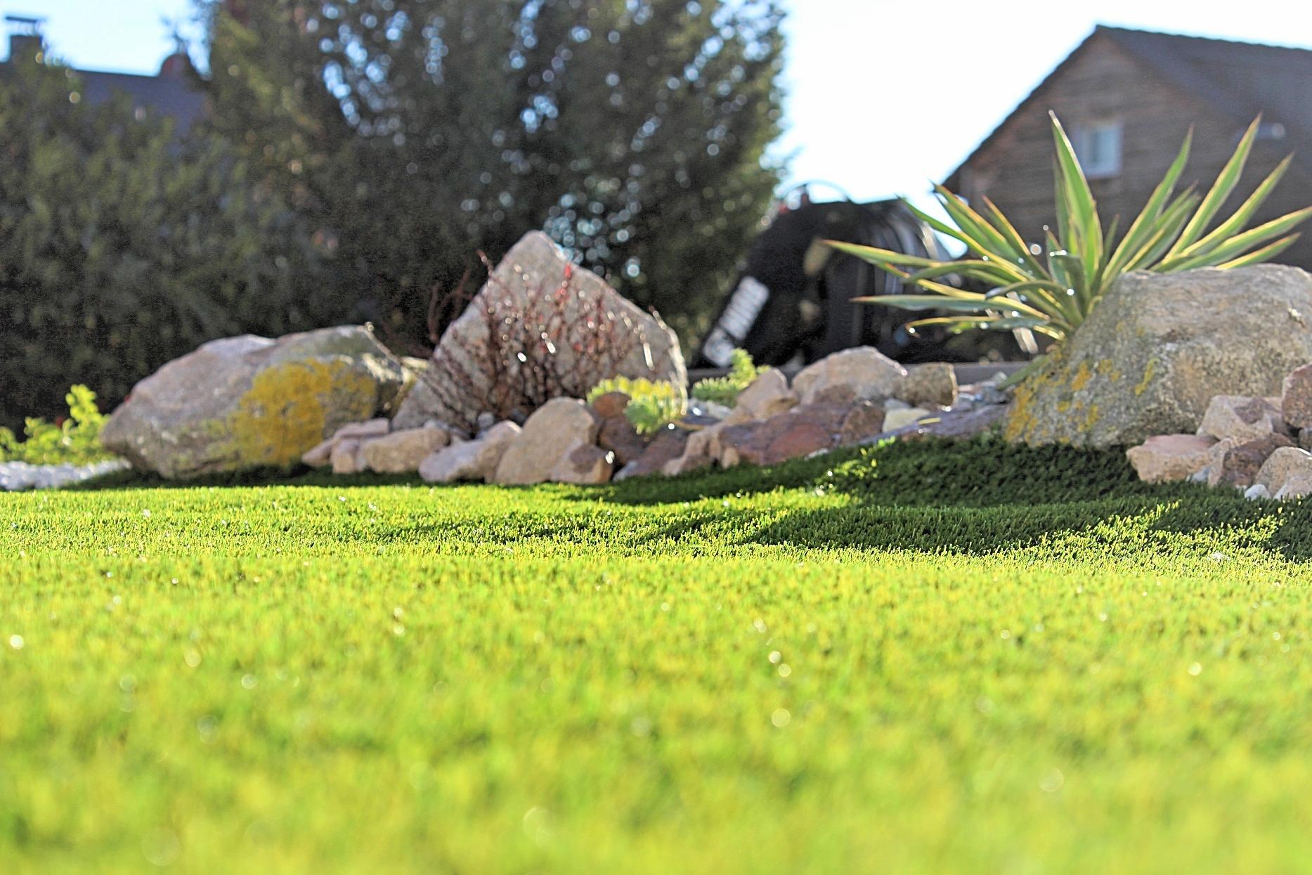 Pflegeleichter Kunstrasen mit Pflanzen und Steinfindlingen