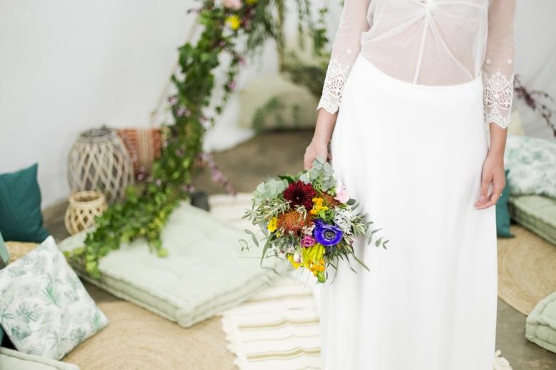 alt novia boho con tipi y ramo de flores