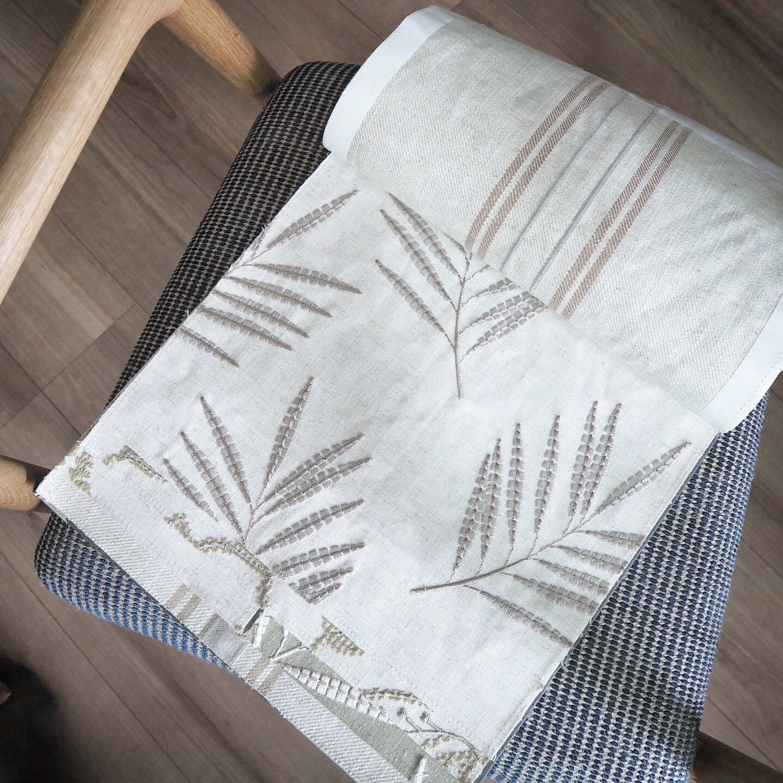 白地にグレーの草木柄の刺繍生地