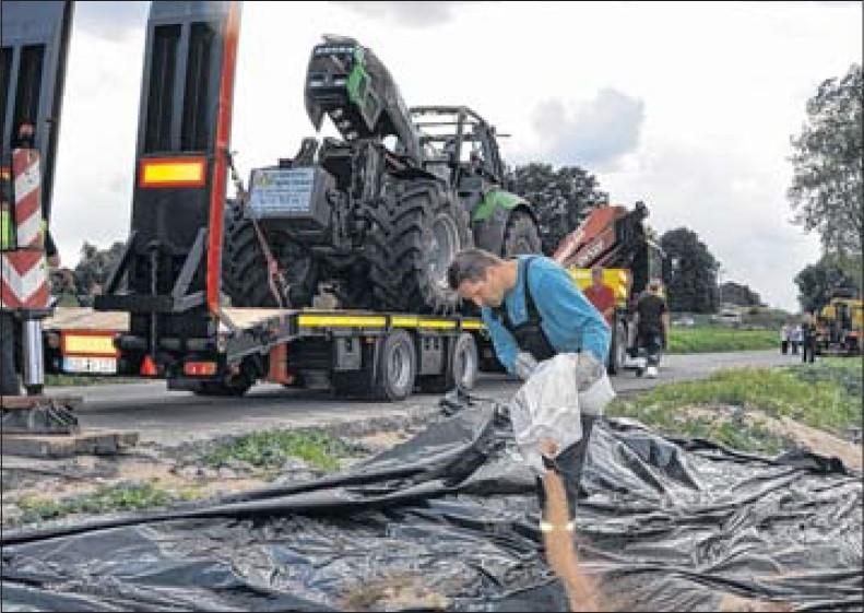 Die Sandauerholzer Feuerwehr bringt Bindemittel auf, nachdem der Traktor auf den Abschlepper gehoben wurde.