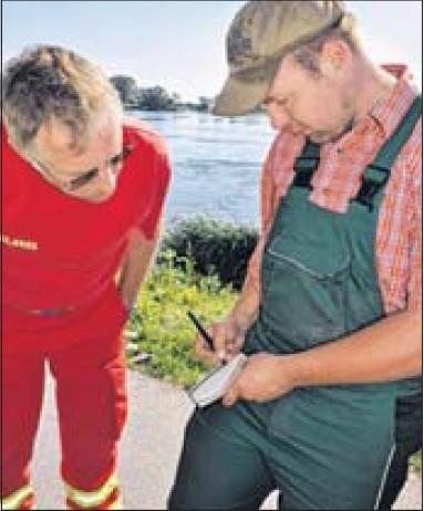 Dietmar Schiess lässt sich von Landwirt Nando Flügel zeigen, wo am Traktor und Hänger die Schäkel für die Seile festgemacht werden können.