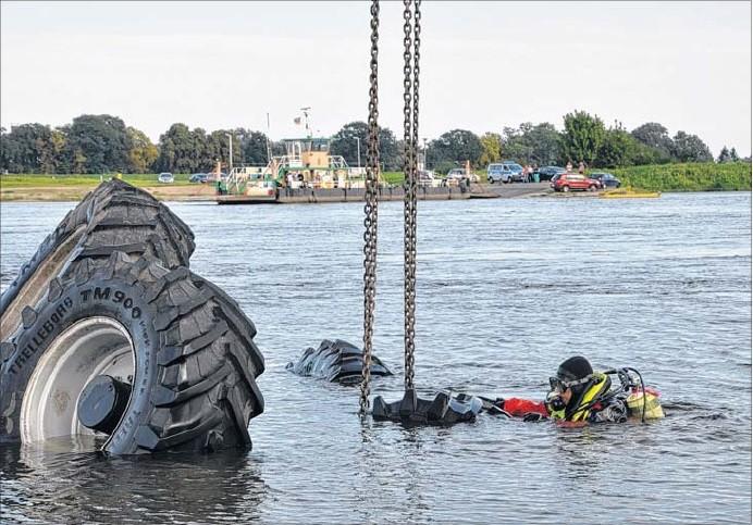 Ein Strömungs-Rettungstaucher der Deutschen Lebensrettungsgesellschaft (DLRG) aus Tangermünde befestigt den Haken eines großen Mobilkrans an dem in der Elbe versunkenen Traktor. Im Hintergrund ist die Sandauer Gierfähre zu sehen.