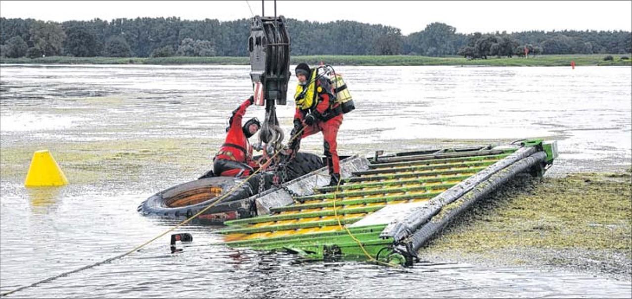 Der Anhänger ist näher ans Ufer gezogen worden. Die Tangermünder Taucher machen die Seile am Haken fest, damit der Kran das Gefährt aus der Elbe hieven kann.