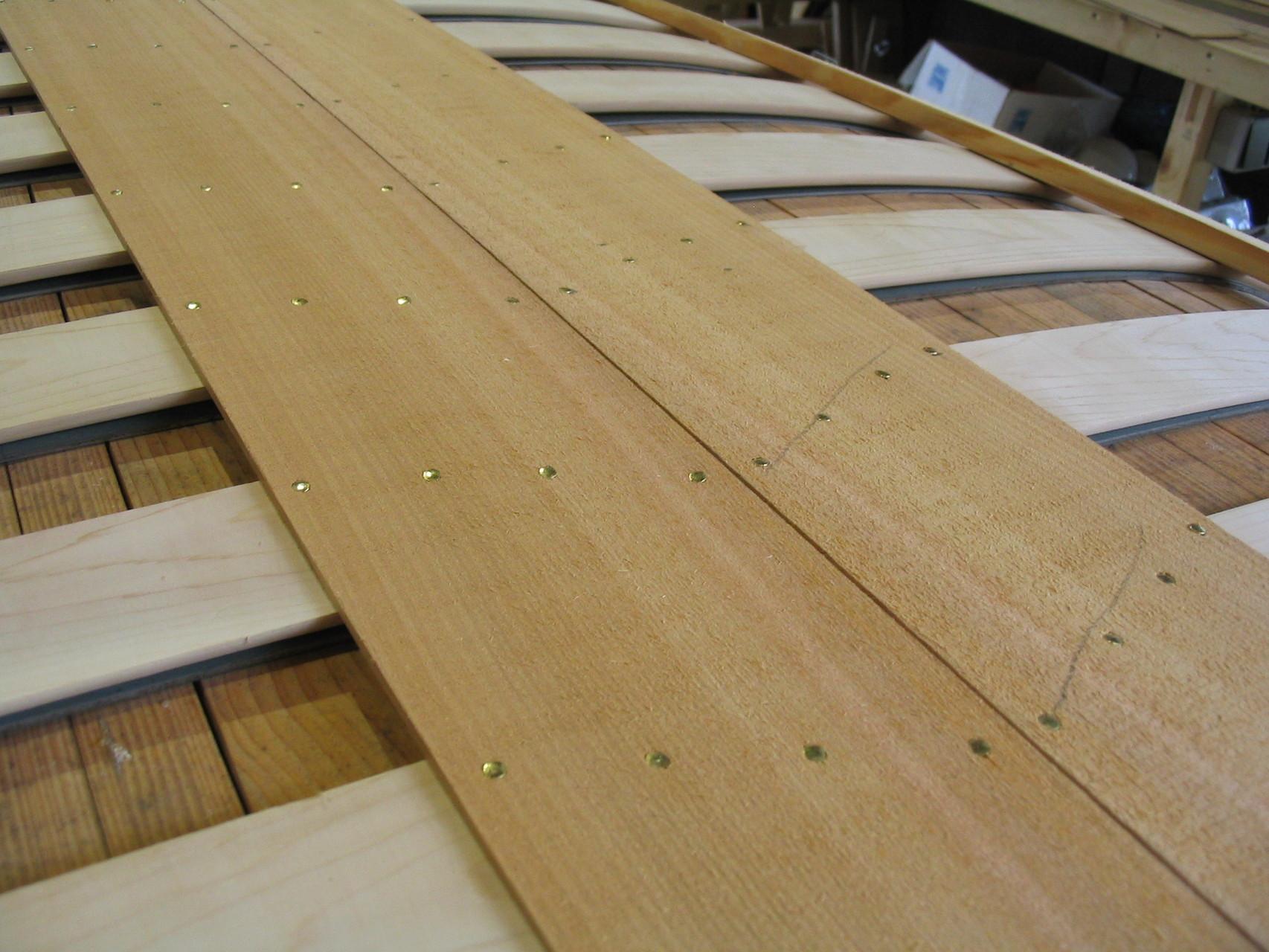 Das Anbringen der Planken gehört wohl zu den schönsten Aufgaben. Hier wird deutlich, wie die enorme Haltbarkeit zustande kommt. Die Nägel werden in gleichmäßigen Abständen durch Planke und Rippe eingeschlagen, sodass sie sich auf dem Stahlband umbiegen.