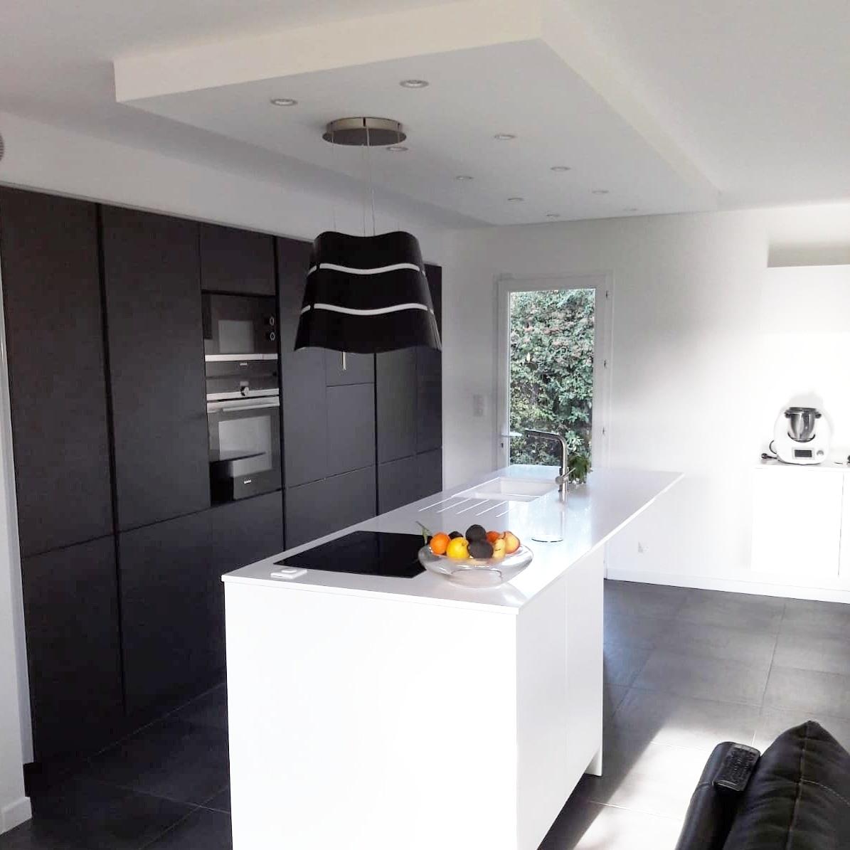 Cuisine noir mate ouverte avec îlot blanc réalisée par Cuisine Intérieur Design Toulouse