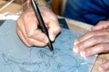①図案をパラフィン紙に線描きし、カーボン紙を使って木に写し取る