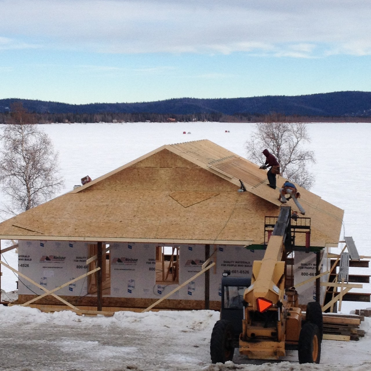 "Last Sunday night, construction above the foundation on this new Harding Lake ""cabin"" had not started.  Today, Friday, March 14, the framing is done, roof trusses on and the roof decking will be done by the end of the day."