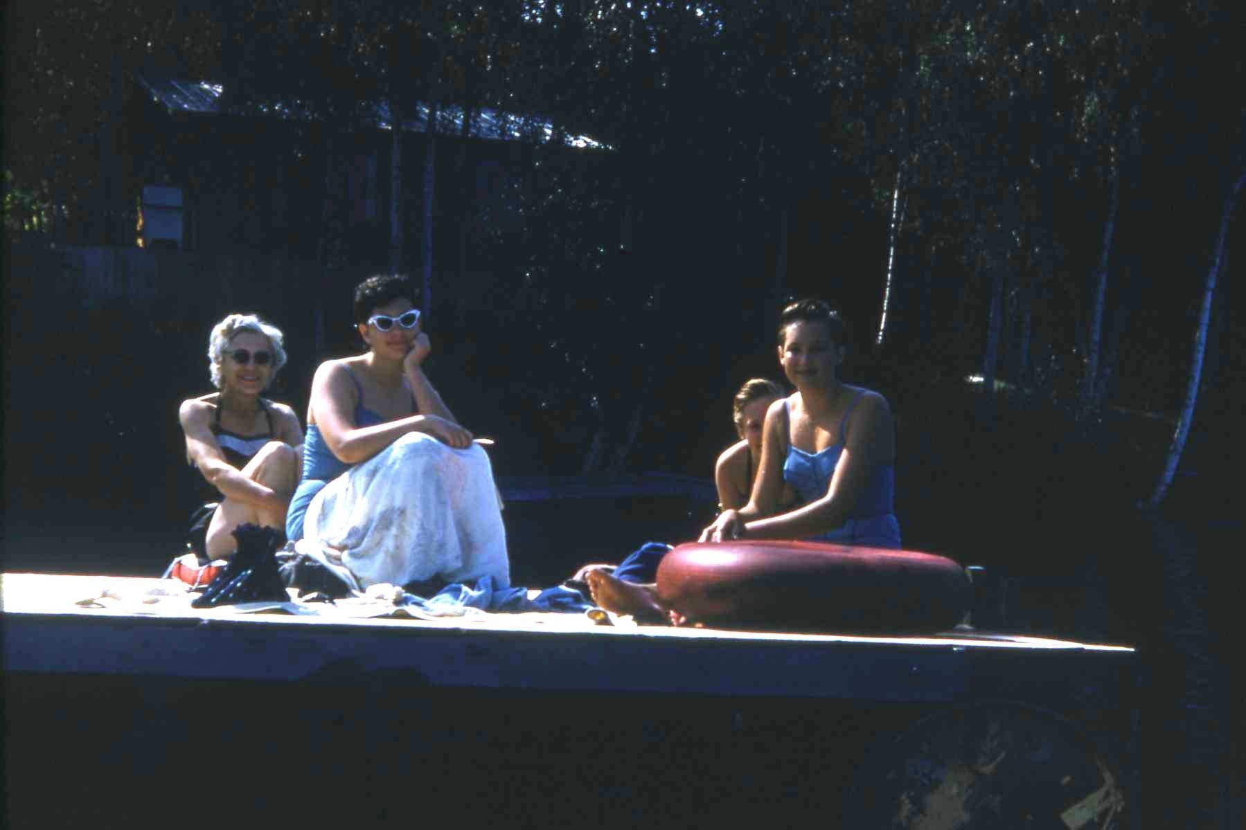 Hazel and Carolyn Clasby, Adele Kohler Virgin and Sue Rank on raft in front of Clasby cabin (where Schok cabins now located at the south end of the lake).1958.